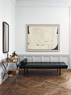 Living space with a gold bar cart and tufted leather daybed