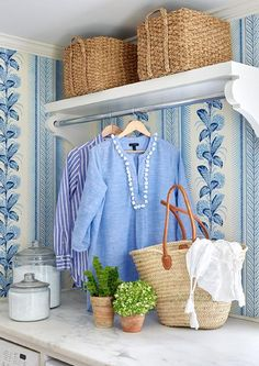 Woven baskets sit on a white shelf fitted with a drying rack and corbels mounted on a wall covered in white and blue wallpaper positioned above a white marble countertop located over a white washer and dryer in this well equipped white and blue laundry room.