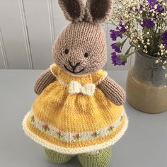 A dress in a sunny yellow with a border of pink buds, and a tiny crochet bow at the waist. This dress was knit with a long cast on of 96 stitches. I knit 14 repeats of the chart pictured on the lef...