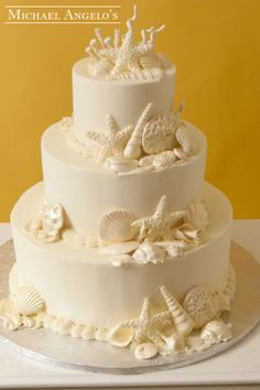 Destination Wedding #34Specialty  This cake is iced in ivory buttercream and smoothed out to look like fondant. The sea shells are made of gum paste and are placed all around the cake to add some depth. Pefect for a destination wedding or your beach theme!