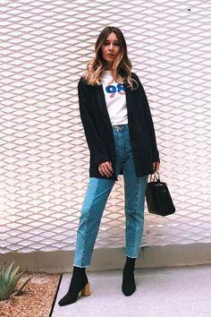 5 modelos de calça jeans que fogem do comum. Suéter preto, t-shirt com estampa vintage, calça bilcolor, jeans desconstruído, ankle boot com salto de blogo de madeira