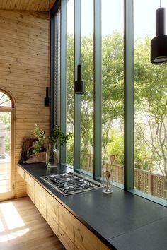 Granit noir et bois du sol au plafond… on aime ce parti pris de matières fortes et naturelles, mises en contraste avec la transparence de grandes baies vitrées, réalisé par Horace Gifford, en 1965, pour la H House. Les suspensions sont d'Alvar Aalto (Artek).