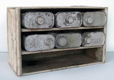 """Tin Can Cubby made from empty tins of mineral spirits, etc, in a custom wooden shelving unit.  The cans are cut open at the top to make little drawers, with the spout serving as the """"handle"""""""