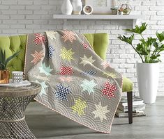 """Gingham Stars. Use the same print in six colorways for a fresh take on a traditional Sawtooth Star block. Designer: Amanda Niederhauser. Finished quilt: 52-1⁄2×64-1⁄2"""". Finished block: 8"""" square."""