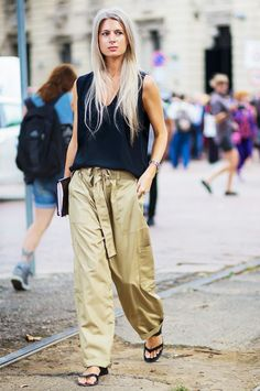 A black tank top is worn with paper bag trousers and slide sandals
