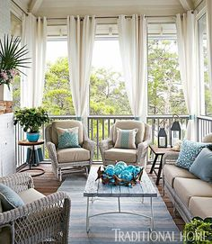 Gorgeous Porch with pops of blue and curtains for summer.
