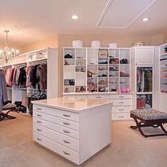 Walk in closet with a table with drawers and a chandelier