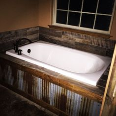 Our rustic bath tub ... Metal tin in front with barn wood tile back splash