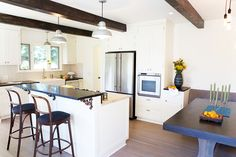 Kitchen with white walls, white cabinets, wood floors, wood barstools, black countertop, white light fixtures, and wooden beams