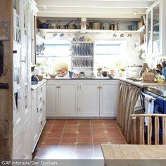Die In Weiß Gehaltene Küche Im Landhausstil Erhält Durch Elemente Wie Den  Ofen Und Geschirr In