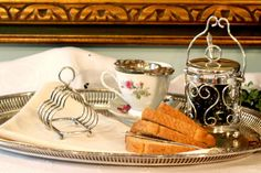What a great find!   A piece very similar to this was featured on Downton Abby; Season #4 episode 7.  It was on Mary's breakfast tray!  This is a smaller size 4 slice English silver plate toast rack.  The five bars are bent into a trefoil shape with a loop handle, sitting on four ball style feet.
