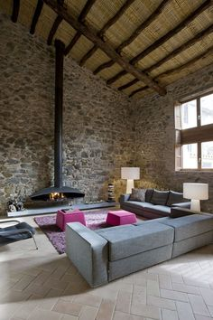 Living room with a fireplace in an Old Mill Transformed into a House and Winery