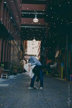 Man dipping his fiancé in an alley