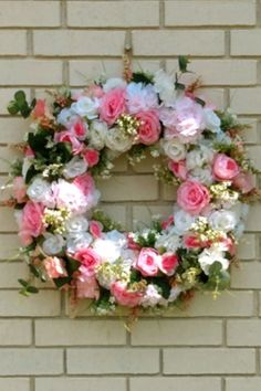 A big beautiful floral wreath lush with pink and white roses, peonies, cherry blossoms and carnations. Lots of leafy greenery, baby's breath and berries, too.