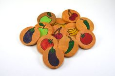 This Montessori-inspired wooden memory game features 12 hard wood pieces hand stamped with 6 different fruits and vegetables. Pieces include a