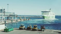 Passenger Ferry Sailing From The Port by Grey_Coast_Media Cruise liner leaving the port. Tractors standing on the pier. Sea traveling and vacation time You can also download this footage i