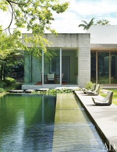 The swimming pool features a chemical-free filtration system, utilizing a separate regeneration area filled with aquatic plants and fish for water purification; the poolside lounges are Willy Guhl cement Loop chairs.