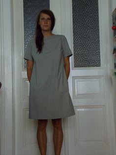 Becasina s mašlí v šedé Šedé minimalistické šaty rovného střihu. Díkysešití v zadní části jsou volné a velmi lehké a příjemně nositelné. Lodičkový výstřih. Všité rukávky. Barevné kapsičky !! Velikost M.