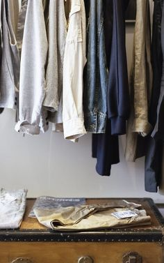 clothes hanging in a closet with a vintage trunk on the floor