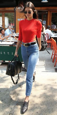 Kendall Jenner stepped out in NYC in a bold persimmon long-sleeve top tucked into belted high-waist denim skinnies, complete with retro round sunnies and black brogues.