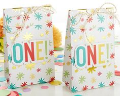 """1st Birthday Tall Treat Box (Set of 24). Treat your guests with our Kate Aspen 1st Birthday Tall Treat Box! Able to be filled with any treats you love, the box is in a tall bag shape, with an all over multi-colored confetti print and white twine tie. An appliqué cutout of the word """"ONE!"""" sits front and center on each tall box! Features and facts:  Tall bag shaped treat box with an all over asterisk confetti print in gold foil, pink, green, blue, red, and yellow. Bags come pre-tied..."""