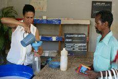 Dependienta de una bodega le despacha la leche a un consumidor