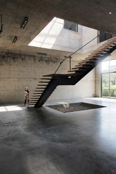 Thai studio ASWA has placed a four-storey atrium with a huge skylight at the centre of this concrete art gallery and studio in Bangkok.