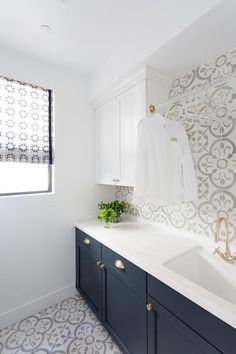 Stunning blue and white laundry boasts floors clad in Granada Normandy Tiles matching a backsplash complementing white shaker upper cabinets fitted with an acrylic and brass drying rod positioned over a curved sink paired with a brass vintage cross handle faucet.