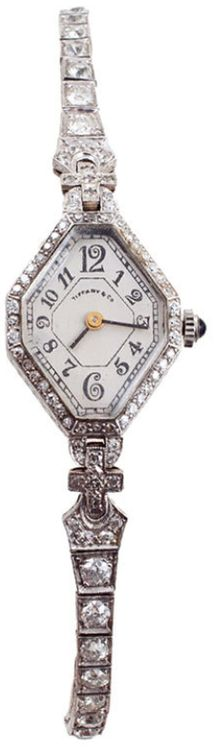 Tiffany & Co. Art Deco Lady's Platinum and Diamond Wristwatch. The hexagonal white watch dial is signed Tiffany & Co. and is bordered by a row of bead-set round diamonds and joined to the bracelet of square links bead-set with larger round diamonds by rectangular cross-shaped links.