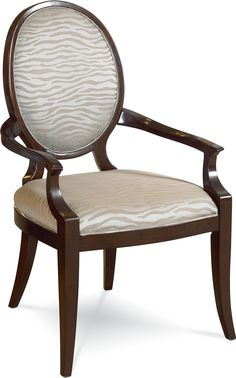 Spellbound Upholstered Arm Chair  Everything comes full circle – or nearly so. The oval-back arm chair completes the Spellbound dining room with no sacrifice of style or creature comforts. Upholstered seat and back are perfectly pitched for long lively dinners. The wood trim harmonizes with the Spellbound dining table.