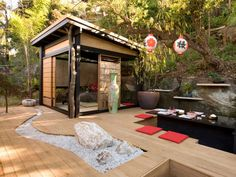 This Japanese-style garden has a tatami room and a sunken dining area. A dry riverbed of crushed quartz and large quartz boulders is cut into the deck. Paper lanterns and a green-and-pink vase add to this outdoor dining area. Instead of standard chairs, guests are invited to sit on red cushions. Design by Jamie Durie