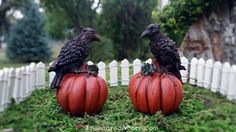 An eerie, imposing crow aggressively claws a grand, round, nearly symmetrical orange pumpkin. Black, brown, and copper tones encompass this