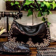 Flower studs and rhinestones glittering on black leather #campomaggi #black #bag #bracelet