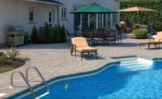 A raised paver patio leads to a paving brick pool deck.