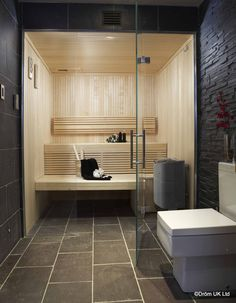 Dröm UK designed and installed this stunning Aspen sauna adjacent to the first floor gym in a Hampshire family home . The sauna is of Aspen throughout with low voltage lighting incorporated into the backrests for added ambience and contrasting large format slate tiles on the floor to match the rest of the decor of the bathroom. The benches have been precision cut around the heater. Frameless glass gives a spacious feel to this sleek, modern room.