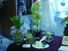 Tropical / Contemporary Centerpieces : Tall elegant Cymbidium Orchids and matching floating ones for a beautiful  table piece... add fresh bamboo plants and you have the oriental and tropical feel!