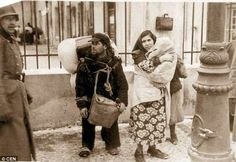 "Lublin. ""A woman holds a child close to her chest alongside a man laden down with belongings as German troops herded residents into cattle trucks to deliver them to their deaths at Belzec or Majdanek."""