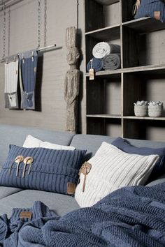 Plaids et coussins bleus se marient admirablement avec le gis des murs pour une ambiance feutrée.