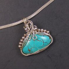 Sterling Silver and Turquoise Wire Wrapped Pendant     The pendant measures 1 5/16 inches long by 1 3/16 inches wide.  One of a kind.