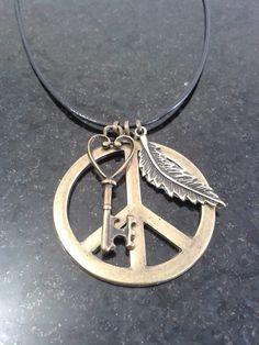 Cordão preto com pingentes símbolo da paz, folha e chave. <br>Fecho mosquetinho