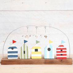 Wooden beach hut and seagull decorationThis coastal themed row of beach huts are an easy way to add some fun, colour and interest to your bathroom or nautical inspired room. Each of the 5 beach huts are individual adding more interest to this great piece. All hand painted in shades of blue, yellow, red and green and given a distressed finish, each hut also has its own metal flag. There are also 3 seagulls hanging from the wire which are movable  Great gift for birthdays, mothers day or…