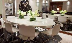 A mesa Saarinen é sempre o centro das atenções. Essa mesa é um ícone do Design.  As cadeiras Amanda em recouro são funcionais e não chamam a atenção para si. Um painel de espelho bisotê foi criado para dar a importante sensação de que o ambiente é mais amplo e trazer um volume necessário a essa parede.