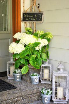Galvanized pots, lanterns, hydrangeas, and chalkboard bring summertime to a porch: HomeDeco50