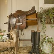 Riding boots and horse tack can give flavor to a backdrop for wedding guest seating cards