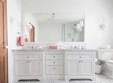 Stunning bathroom features a crisp white wall lined with a full length white vanity mirror illuminated by Robert Abbey The Muses Calliope 1 Light Wall Sconces situated over a white dual washstand topped with gray and white marble fitted with his and her sinks atop a Saltillo Imports Long Octagon Tile floor next to a faux stag head placed over the toilet.