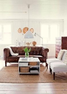 Brown leather couch + sisal rug + white occasional chairs + white beadboard walls + vintage industrial lighting