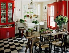 umm this kitchen is a dream - bright reds on the cabinets, black and white checked floors, wooden tabletops all against a big, white kitchen