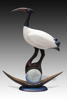 Ibis Moon Barq by Dona Dalton. The ibis, the totem animal of the ancient Egyptian moon god, Thoth, is represented in this mythological sculpture. Carved poplar and pine wood is painted with acrylic enamel. Top of boat is detailed with metallic leaf.