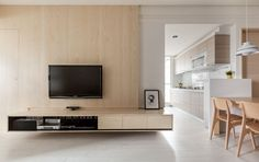 A flat panel television is mounted into a wood paneled wall, suspended above a floating wooden entertainment center.