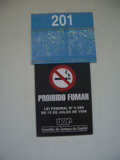 "Aviso de ""Proibido Fumar"" afixado na parede,destina-se aos fumantes do local. A mensagem é frisada pelo símbolo característico."